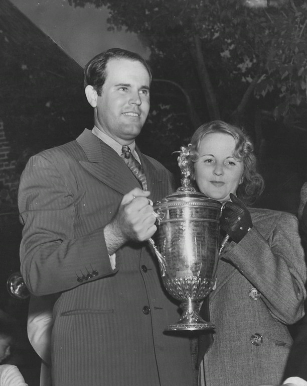 . Ralph Guldahl, named to the Professional Golfers Association Hall of Fame, is shown with wife accepting the championship trophy after his victory in the 1938 U.S. Open Golf Championship at the Cherry Hills Country Club. Denver Post Library photo archive