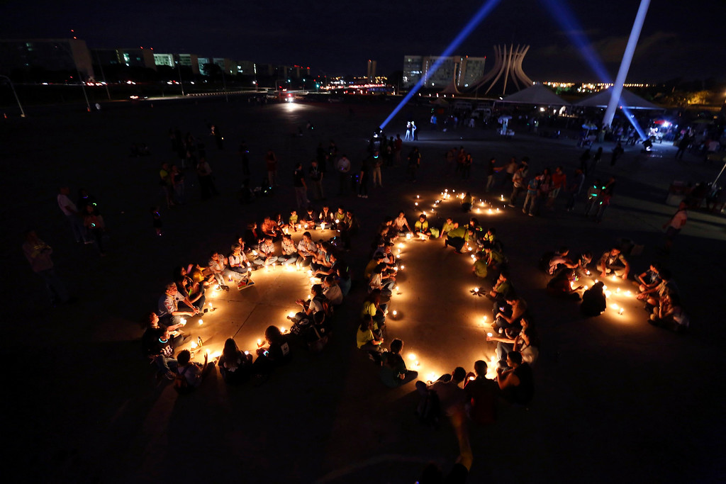 . People gather with candles during an event of Earth Hour, organized by WWF Brazil, at the Museum of the Republic in Brasilia March 23, 2013. Earth Hour, when everyone around the world is asked to turn off the lights for an hour from 8.30 pm local time, is meant as a show of support for tougher actions to combat climate change. REUTERS/Ueslei Marcelino