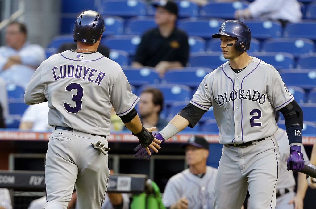 . Colorado Rockies\' Michael Cuddyer (3) is met by teammate Troy Tulowitzki (2) after scoring on a double hit by Carlos Gonzalez in the first inning of a baseball game against the Miami Marlins, Wednesday, April 2, 2014, in Miami. (AP Photo/Lynne Sladky)