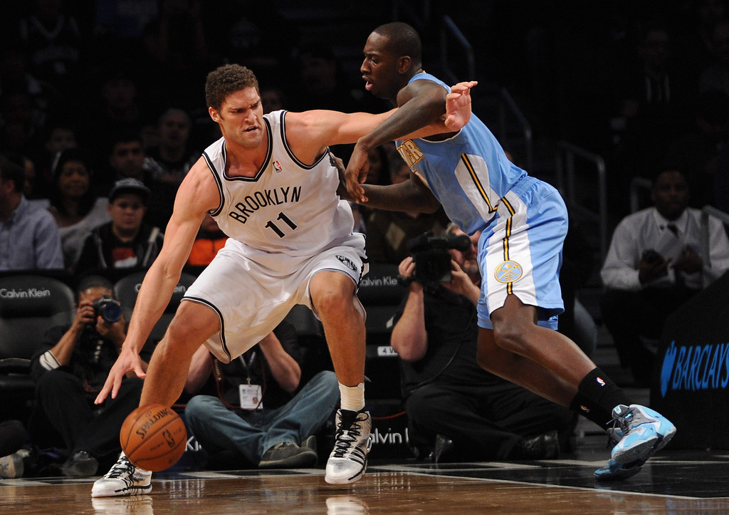 . NEW YORK, NY - DECEMBER 03:  Brook Lopez #11 of the Brooklyn Nets dribbles against J.J. Hickson #7 of the Denver Nuggets during the first quarter at Barclays Center on December 3, 2013 in the Brooklyn borough of New York City.  (Photo by Maddie Meyer/Getty Images)