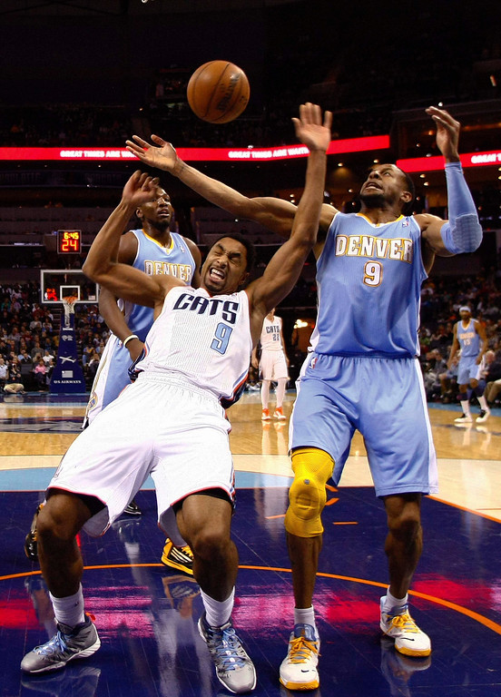 . Charlotte Bobcats shooting guard Gerald Henderson (front L) reacts as he fights for a rebound against Denver Nuggets shooting guard Andre Iguodala (R) during the first half of their NBA basketball game in Charlotte, North Carolina February 23, 2013. REUTERS/Chris Keane