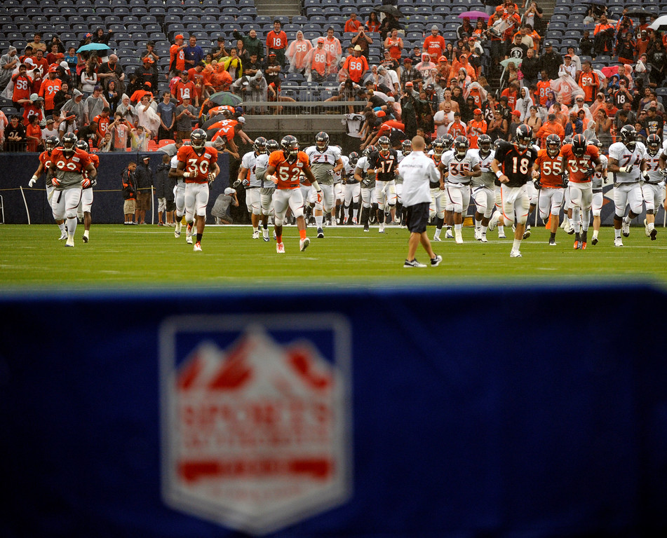 . DENVER, CO. - AUGUST 03: Peyton Manning led the team onto the field even as the rain continued to fall. The Denver Broncos practiced in the rain at Sports Authority Field Saturday night, August 3, 2013. Photo By Karl Gehring/The Denver Post
