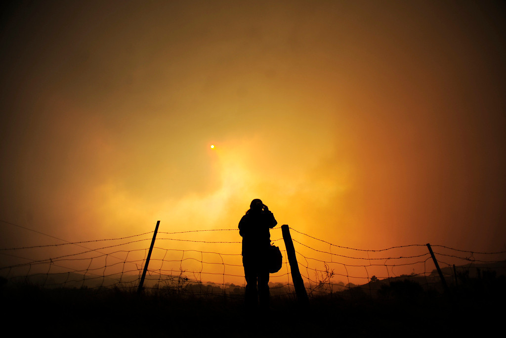 . Crystal Foust watches from County Road 56 as the High Park fire burns west of Fort Collins and Loveland on Sunday, June 10, 2012. The rapidly growing High Park fire is now burning an estimated 2,000 to 3,000 acres west of Fort Collins and Loveland, according to the Larimer County Sheriff�s Office. AAron Ontiveroz, The Denver Post