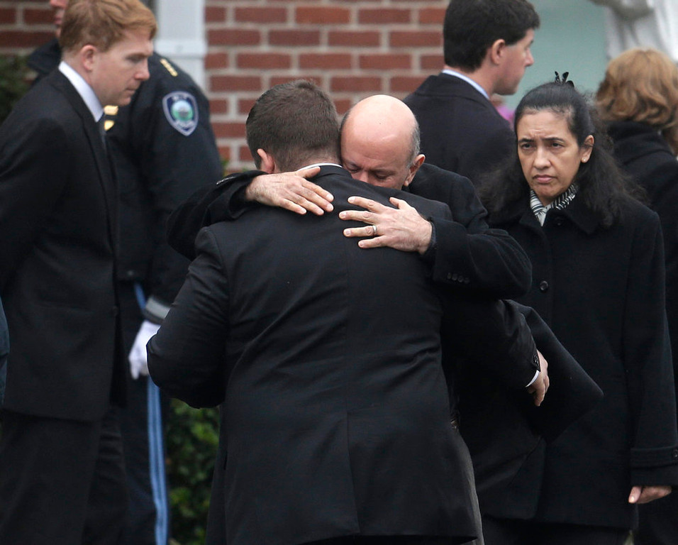 . Mourners hug as they depart St. Patrick\'s Church in Stoneham, Mass., following a funeral Mass for Massachusetts Institute of Technology police officer Sean Collier, Tuesday, April 23, 2013. Collier was fatally shot on the MIT campus Thursday, April 18, 2013. Authorities allege that the Boston Marathon bombing suspects were responsible. (AP Photo/Steven Senne)