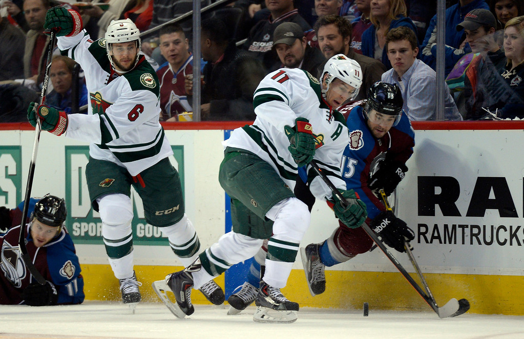 . Minnesota Wild left wing Zach Parise (11) and Colorado Avalanche right wing P.A. Parenteau (15) battle for the puck down the boards during the second period. (Photo by John Leyba/The Denver Post)