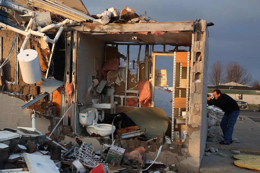 . A man takes a photo of a damaged building along Washington Road in the aftermath of a tornado on November 18, 2013 in Washington, Illinois. A fast-moving storm system that produced several tornadoes that touched down across the Midwest left behind a path of destruction in 12 states.  (Photo by Tasos Katopodis/Getty Images)