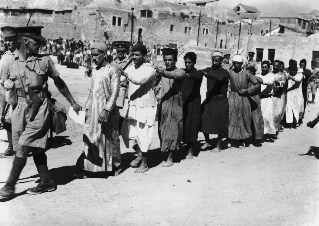 . British soldiers escort a group of Arab prisoners from the Old City of Jerusalem after a revolt against the British mandate in Palestine, 26th October 1938. (Photo by Central Press/Hulton Archive/Getty Images)