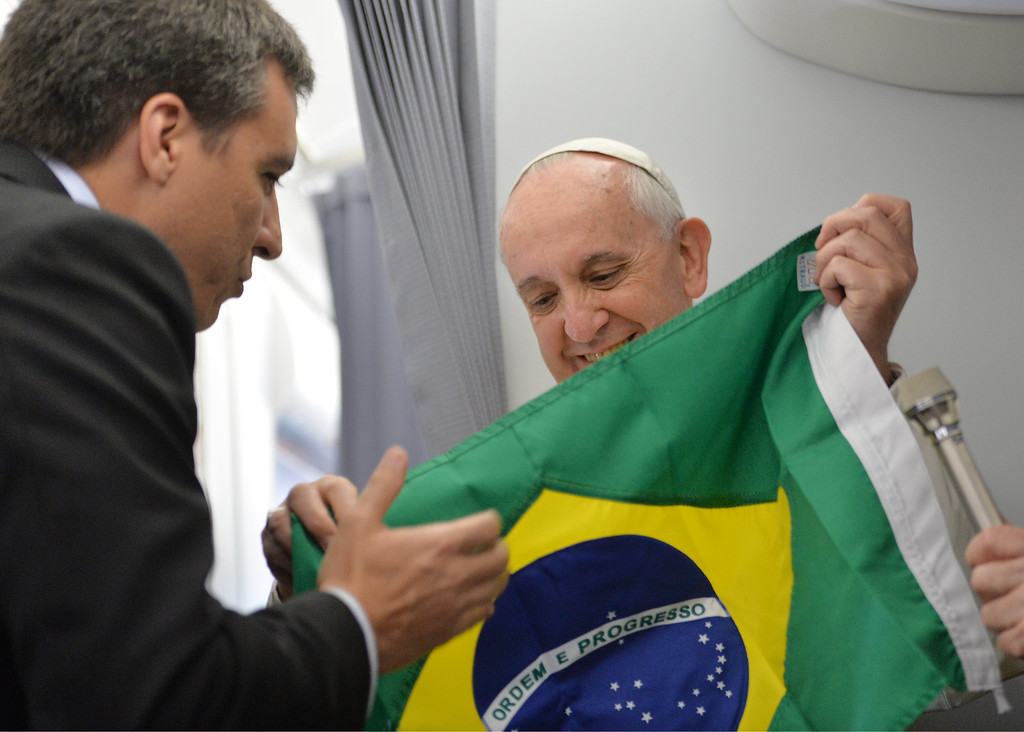 . Pope Francis accepts a Brazilian flag from journalists during the direct papal flight to Rio de Janeiro, Monday, July 22, 2013.   (AP Photo/Luca Zennaro, Pool)