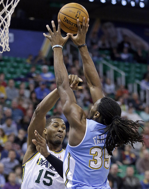 . Denver Nuggets\' Kenneth Faried (35) blocks the pass of Utah Jazz\'s Derrick Favors (15) in the first quarter during an NBA basketball game, Monday, Jan. 13, 2014, in Salt Lake City. (AP Photo/Rick Bowmer)