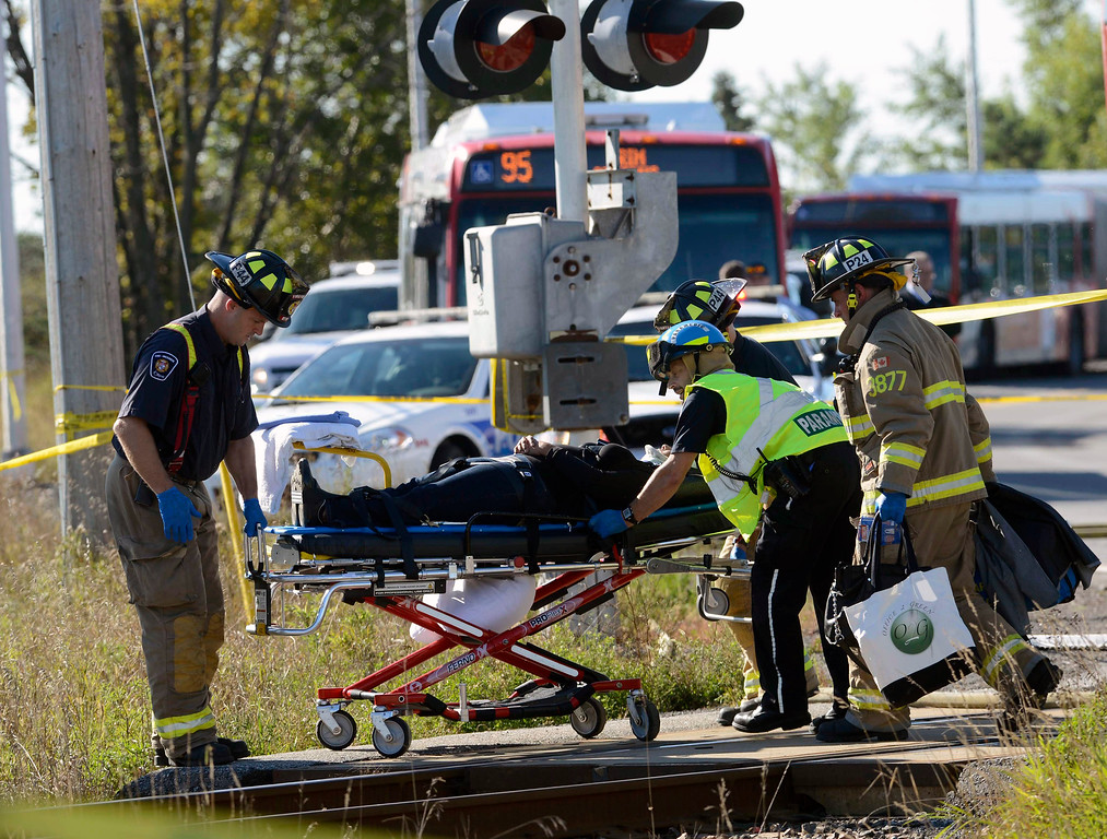 . A passenger is taken to an ambulance at the scene of a collision with a train and a city bus in Ottawa, Ontario, Wednesday, Sept. 18, 2013. An Ottawa Fire spokesman said there are ìmultiple fatalitiesî and a number of people injured from the bus. (AP Photo/The Canadian Press, Adrian Wyld)