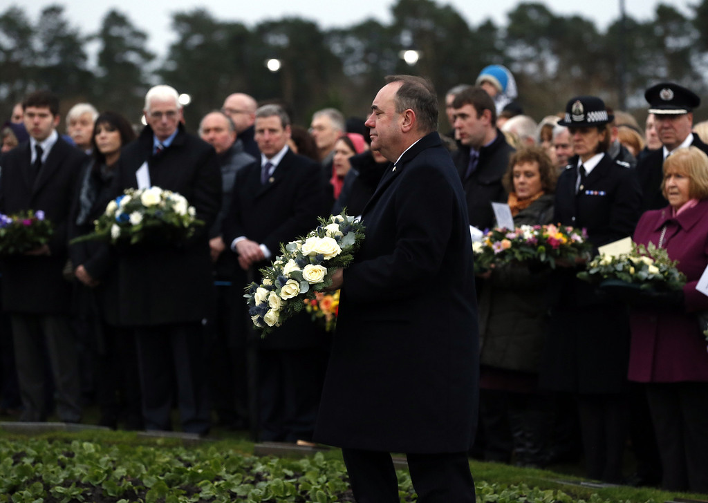 . Scotland\'s First Minister Alex Salmond carries a wreath to the main memorial stone in memory of the victims of the Lockerbie Pan Am flight 103 bombing in the garden of remembrance at Dryfesdale Cemetery, near Lockerbie, Scotland. Saturday Dec. 21, 2013.  (AP Photo/Scott Heppell).