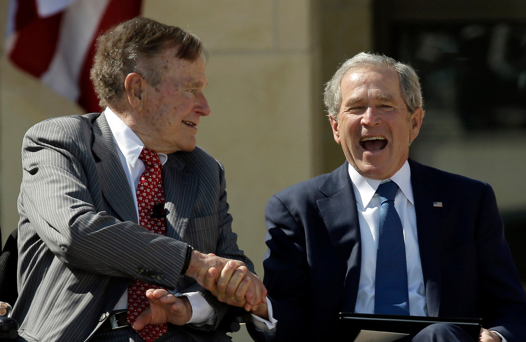 . Former President George H.W. Bush shakes hands with his son, former President George W. Bush during the dedication of the George W. Bush Presidential Center, Thursday, April 25, 2013, in Dallas. (AP Photo/David J. Phillip)