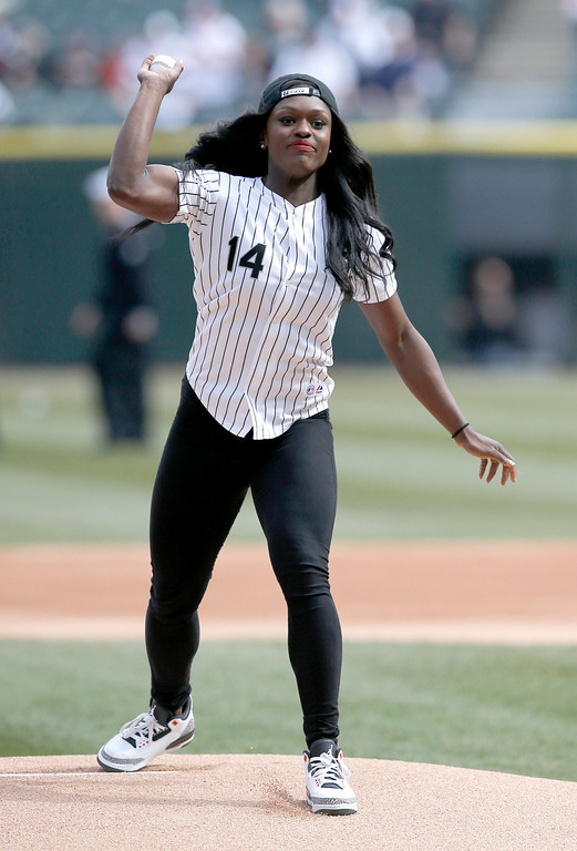 . Olympian Aja Evans throws out a ceremonial first pitch before an opening day baseball game between the Chicago White Sox and the Minnesota Twins Monday, March 31, 2014, in Chicago. (AP Photo/Charles Rex Arbogast)