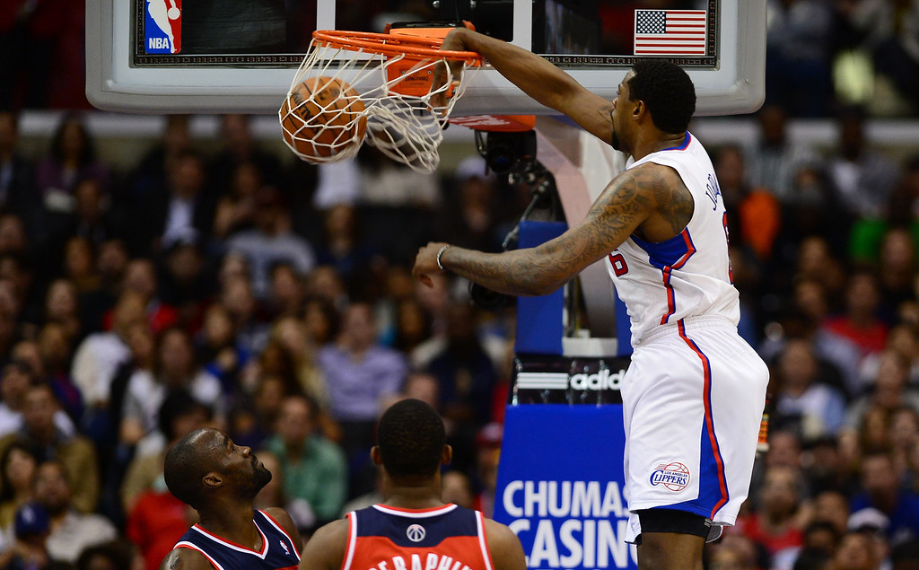 . DeAndre Jordan of the Los Angeles Clippers scores with a slam dunk as Emeka Okafor (L) and Kevin Seraphin (C) of the Washington Wizards watch during their NBA game in Los Angeles on January 19, 2013.  AFP PHOTO / Frederic J. BROWNFREDERIC J. BROWN/AFP/Getty Images