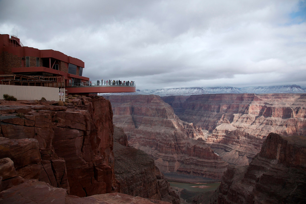 . Visitors have a view of the Grand Canyon and the Colorado River flowing below from a skywalk extending out over the Grand Canyon and its incomplete building, on the Hualapai Indian Reservation, Arizona February 28, 2012.  The tiny Hualapai nation, in a bold move that could serve as a test of the limits of the sovereign power of Native American tribes over non-members, exercised its right of eminent domain last month to take over the management of the site and kick out the non-Indian developer. The dispute over the potentially lucrative Skywalk -- which all agree could draw up to 3,000 visitors a day -- pits the tribe\'s sovereign rights over a site it sees as its economic lifeblood against a developer\'s contractual right to manage the attraction for 25 years and share the profits.   REUTERS/Robert Galbraith