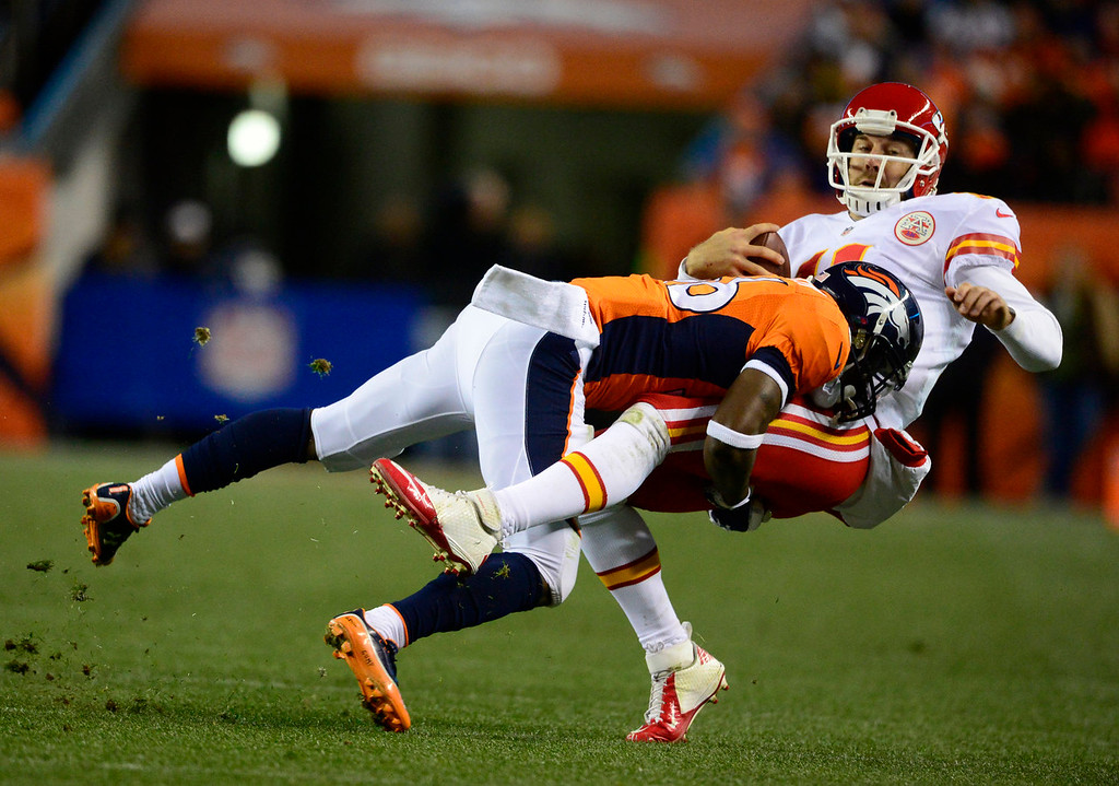 . Kansas City Chiefs quarterback Alex Smith (11) is hit by Denver Broncos cornerback Kayvon Webster (36) in the third quarter. The Denver Broncos take on the Kansas City Chiefs at Sports Authority Field at Mile High in Denver on November 17, 2013. (Photo by AAron Ontiveroz/The Denver Post)