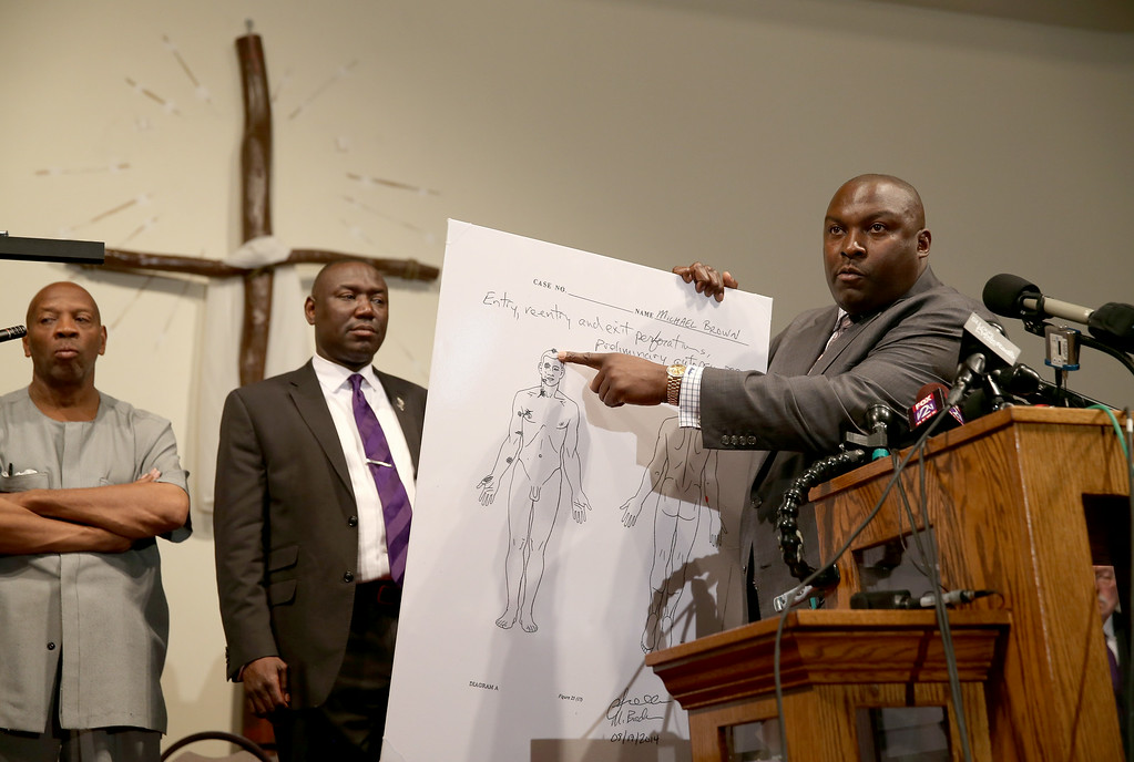 . Michael Brown\'s  family attorney\'s Benjamin Crump (2nd L) and Daryl Parks announce the findings of an autopsy during a press conference at  the Greater St. Marks Family Church on August 18, 2014 in Ferguson, Missouri. Unarmed teenager Michael Brown was shot and killed by a Ferguson police officer on August 9th.  (Photo by Joe Raedle/Getty Images)