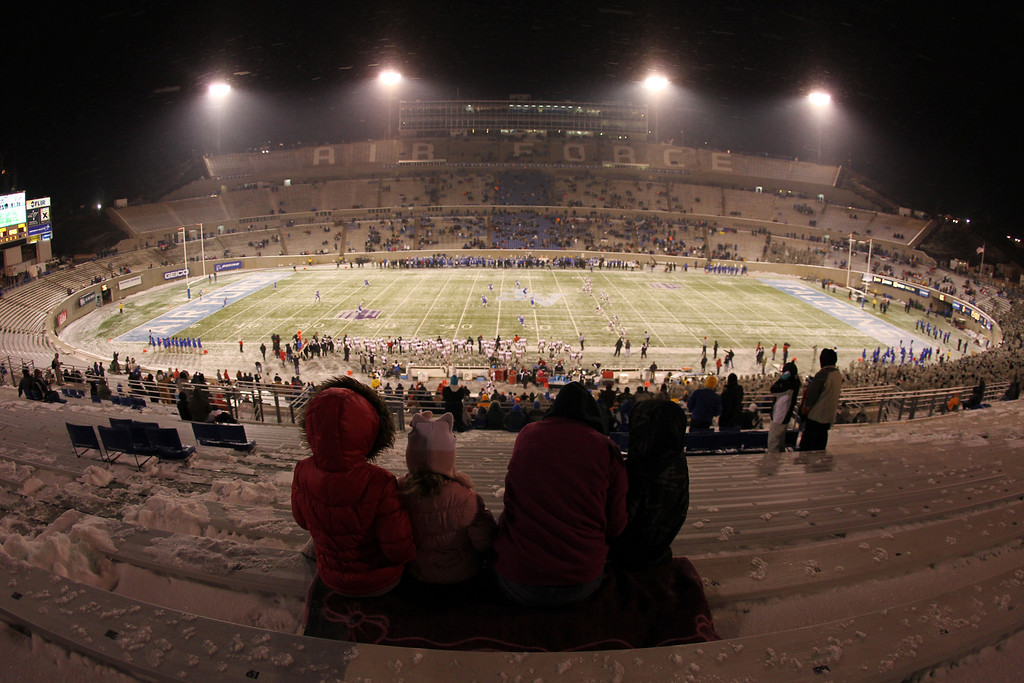. Fans huddle together in the near-empty stands as UNLV kicks off to Air Force in the first quarter of an NCAA football game at Air Force Academy, Colo., on Thursday, Nov. 21, 2013. (AP Photo/David Zalubowski)