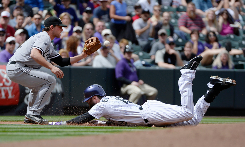 . Colorado Rockies player, Charlie Blackmon, right, beats the throw to Chicago White Sox third baseman, Conor Gillaspie, for a triple in the first inning at Coors Field Wednesday afternoon, April 09, 2014. (Photo By Andy Cross / The Denver Post)