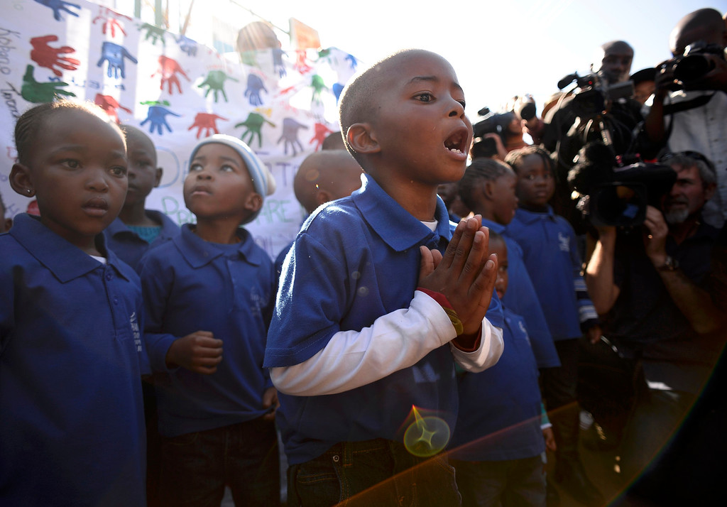 . A student chants a prayer as his class visits Medi-Clinic Heart Hospital to pay respect where ailing former South African President Nelson Mandela is being treated in Pretoria June 26, 2013.    REUTERS/Dylan Martinez