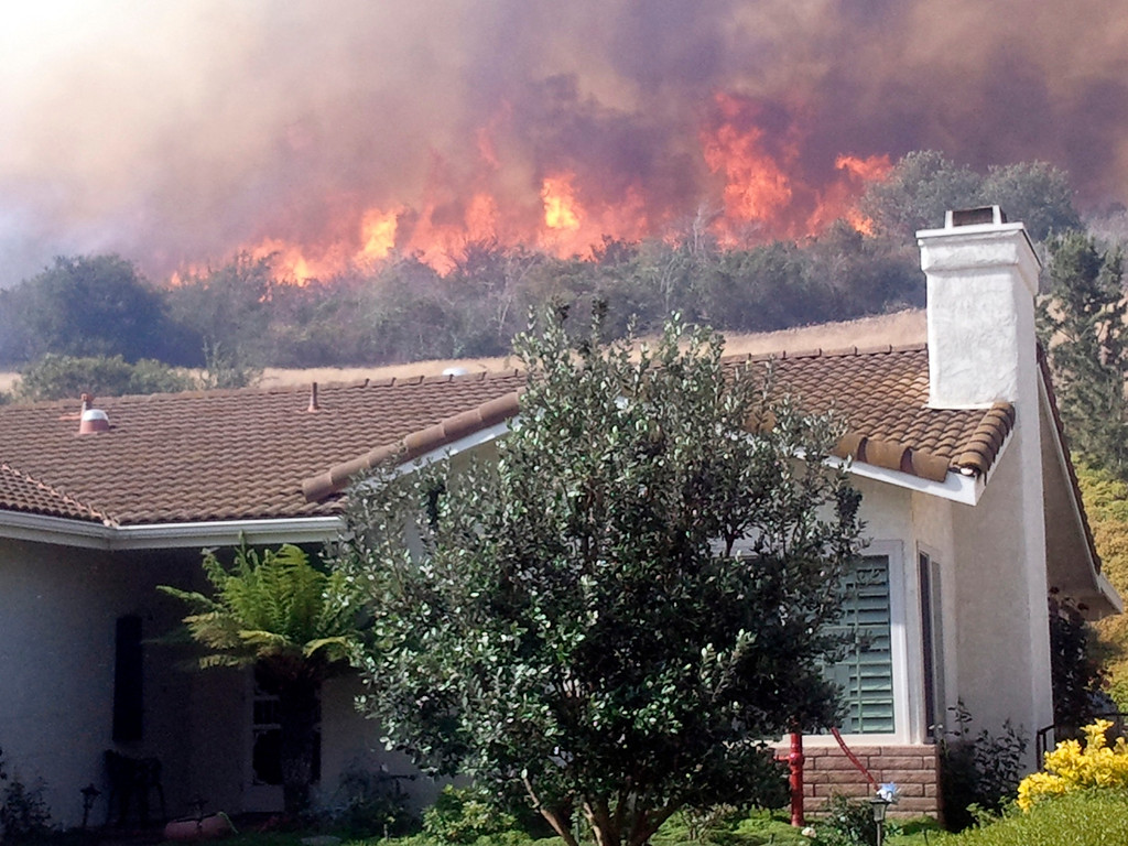 . A fast moving brush fire approaches a home in the Newbury Park area area of Ventura County, California May 2, 2013.  REUTER/Gene Blevins