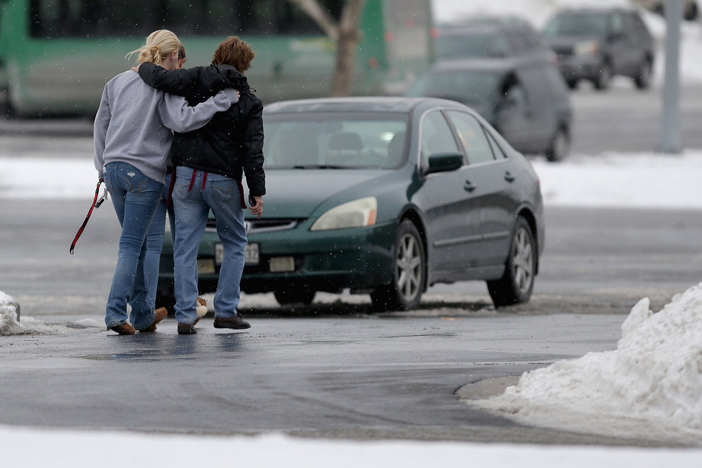 . People embrace each other outside the Columbia Town Center Mall after three people were killed in a shooting there January 25, 2014 in Columbia, Maryland. Police still do not have a motive for the shooting but believe the shooter has been killed.  (Photo by Chip Somodevilla/Getty Images)