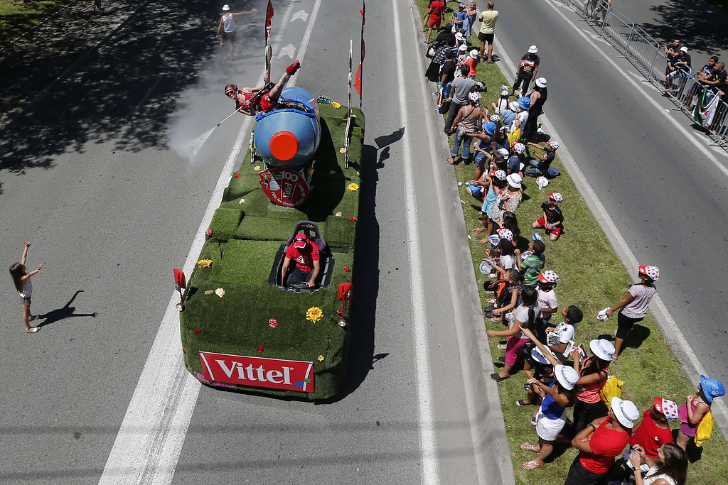 . A woman sprays water on spectators from a Vittel vehicle belonging to the Tour de France advertising caravan before the start of the 25 km team time-trial and fourth stage of the 100th edition of the Tour de France cycling race on July 2, 2013 around Nice, southeastern France.  AFP PHOTO / JOEL SAGETJOEL SAGET/AFP/Getty Images