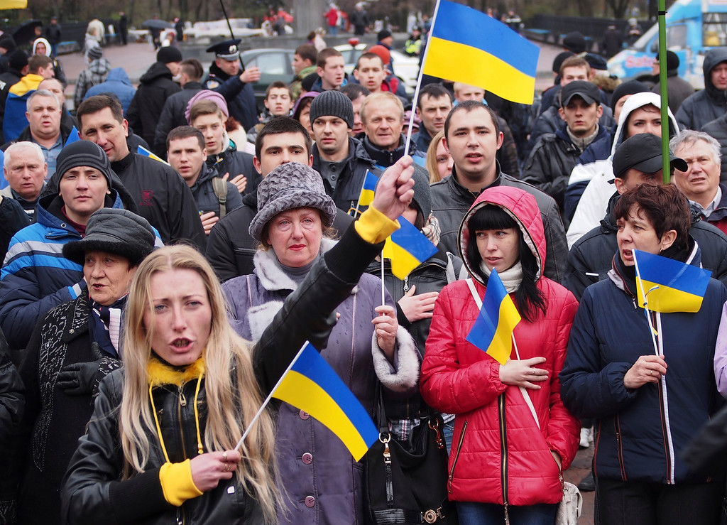 ". Demonstrators wave Ukrainian national flags during a pro-Ukraine rally in Luhansk, 30 kilometers (20 miles) west of the Russian border, Ukraine, Sunday, April 13, 2014. Ukraine is launching a ""large-scale anti-terrorist operation\"" to resist attacks of armed pro-Russian forces, Ukraine\'s President Oleksandr Turchynov said on Sunday in a televised address.(AP Photo/Igor Golovniov)"