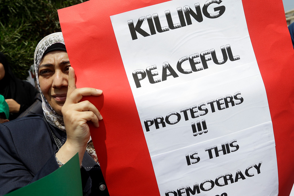 . A Lebanese supporter of the Islamic Group, a Lebanese faction linked to the Muslim Brotherhood, holds a placard during a protest to support the Egyptian protesters of the ousted Islamist President Mohammed Morsi, in front the Egyptian embassy, in Beirut, Lebanon, Wednesday, Aug. 14, 2013.  (AP Photo/Hussein Malla)