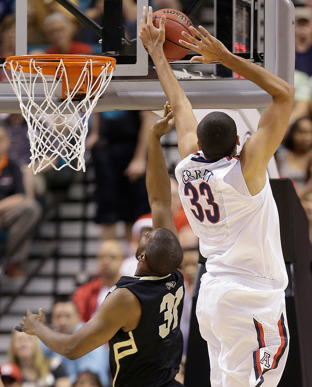 . Arizona\'s Grant Jerrett (33) blocks a shot by Colorado\'s Matt Korcheck in the first half during a Pac-12 tournament NCAA college basketball game, Thursday, March 14, 2013, in Las Vegas. (AP Photo/Julie Jacobson)