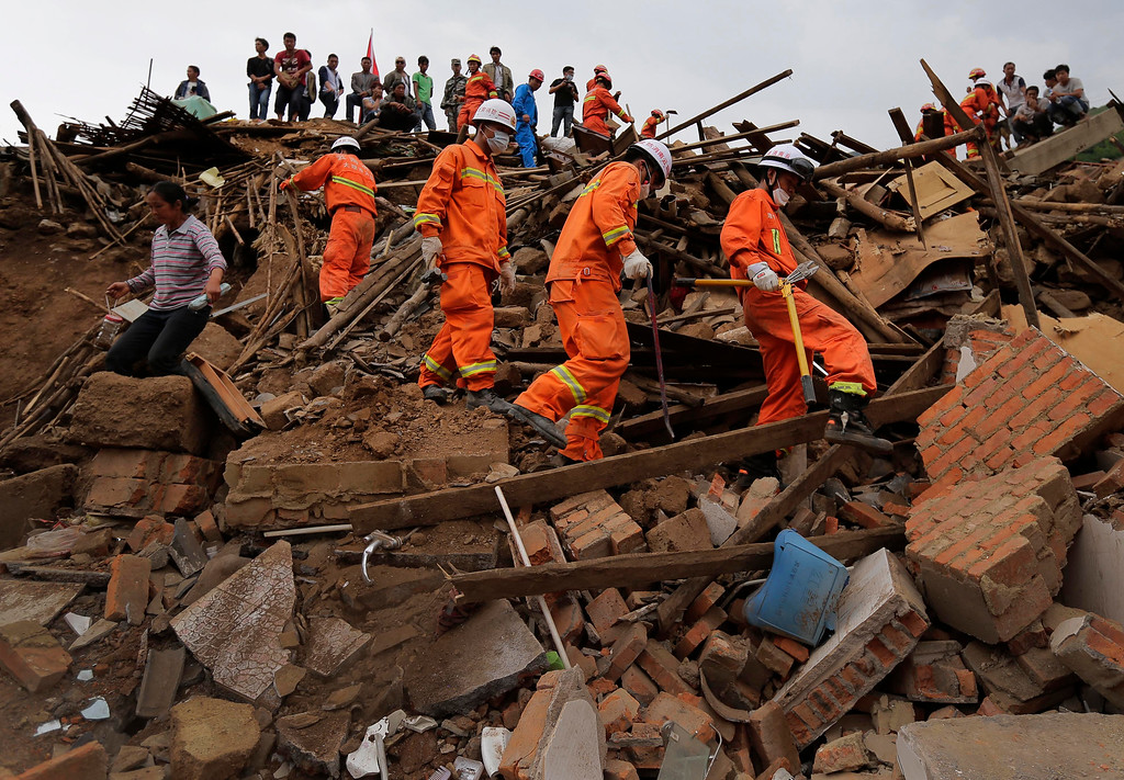 . Rescuers and a villager walk past rubbles from destroyed houses following a massive earthquake in the town of Longtoushan in Ludian County in southwest China\'s Yunnan Province Tuesday, Aug. 5, 2014. (AP Photo/Andy Wong)