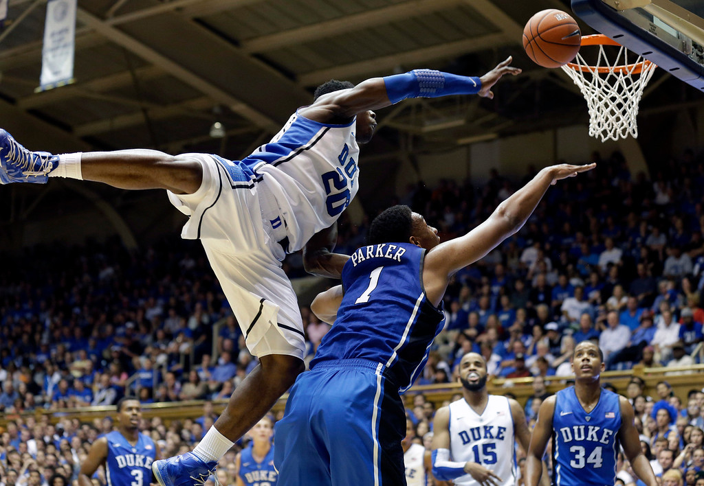 . Duke White team\'s Semi Ojeleye (20) jumps over Blue team\'s Jabari Parker (1) in the Blue-White scrimmage during the team\'s Countdown to Craziness NCAA college basketball preseason event in Durham, N.C., Friday, Oct. 18, 2013. (AP Photo/Gerry Broome)