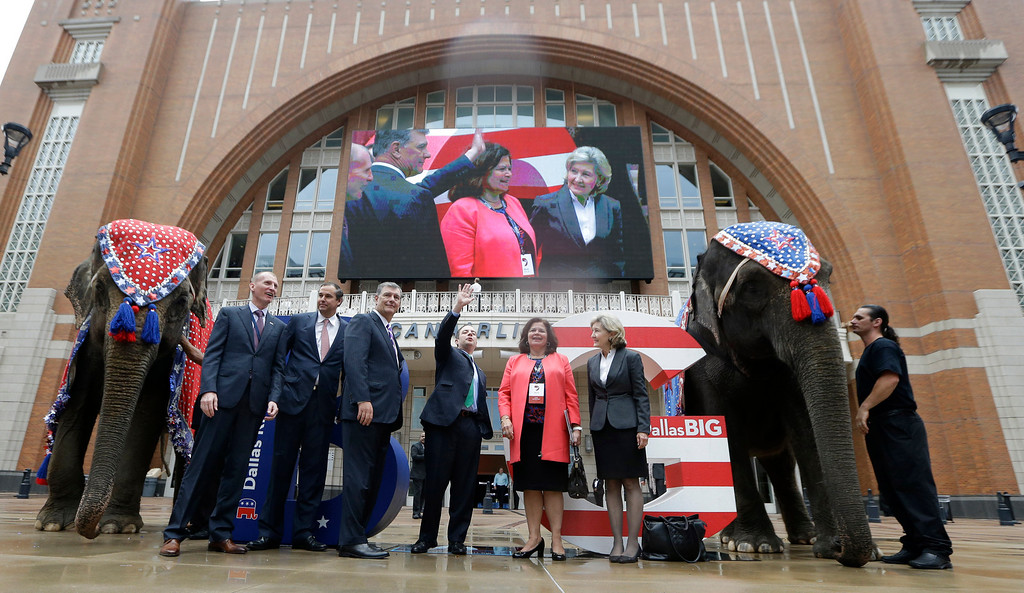 . Posing with live elephants, Republican National Committee chairman Reince Priebus, center right, waves with, from left, Phillip Jones, Ray Washburne, Dallas Mayor Mike Rawlings,  Enid Mickelsen and former U.S. Sen. Kay Bailey Hutchison in front of the American Airlines Center during a visit by members of the Republican National Committee scouting a 2016 Convention host site in Dallas, Thursday, June 12, 2014. American Airlines Center would serve as the convention site if Dallas\' bid is successful. Dallas is competing with Denver, Cleveland and Kansas City. (AP Photo/LM Otero)