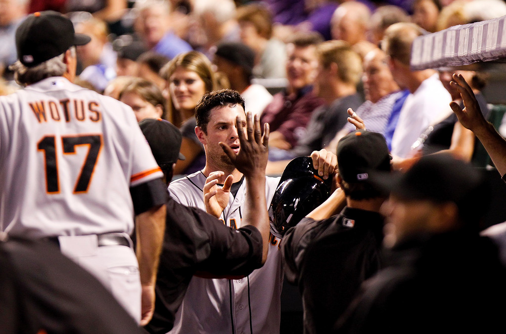 . San Francisco Giants\' Brandon Belt, center, is congratulated by teammates in the dugout after scoring on a grounder by Hunter Pence during the fifth inning of a baseball game against the Colorado Rockies Wednesday, Aug. 28, 2013, in Denver. (AP Photo/Barry Gutierrez)