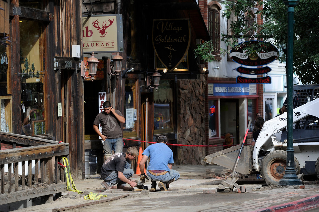 . ESTES PARK, CO - SEPTEMBER 18: Workers replace bricks on a flood damaged sidewalk in front of several businesses along W. Elkhorn Ave in downtown Estes Park Colorado  Tuesday afternoon, September 17, 2013. (Photo By Andy Cross/The Denver Post)