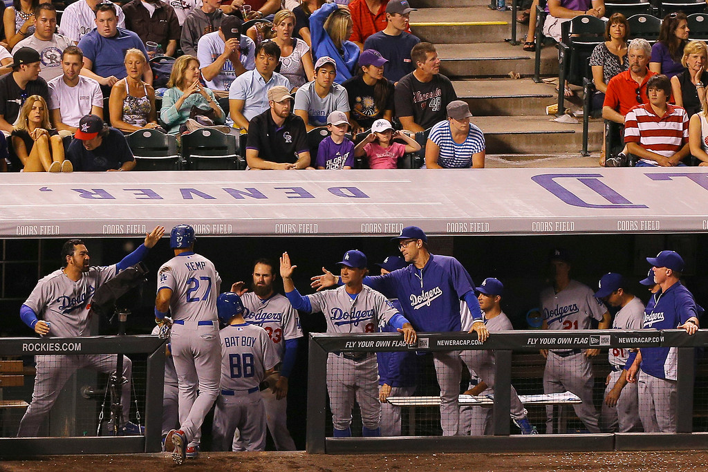 . Matt Kemp #27 of the Los Angeles Dodgers is greeted at the top of the dugout after scoring the eventual game winning run during the eighth inning against the Colorado Rockies at Coors Field on July 3, 2014 in Denver, Colorado. The Dodgers defeated the Rockies 3-2. (Photo by Justin Edmonds/Getty Images)