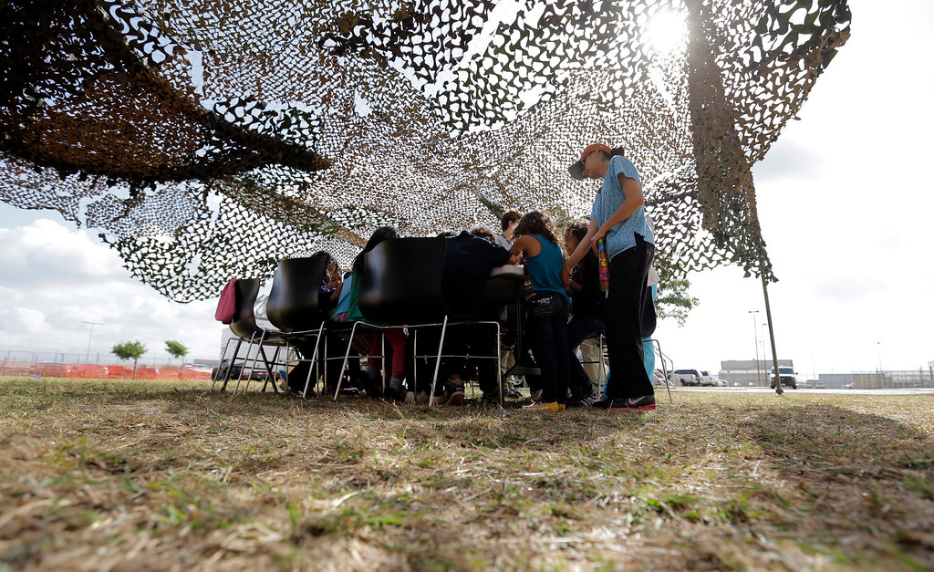 . Detainees do art work under a camouflage tent at a U.S. Customs and Border Protection processing facility, Wednesday, June 18, 2014, in Brownsville,Texas.  (AP Photo/Eric Gay, Pool)