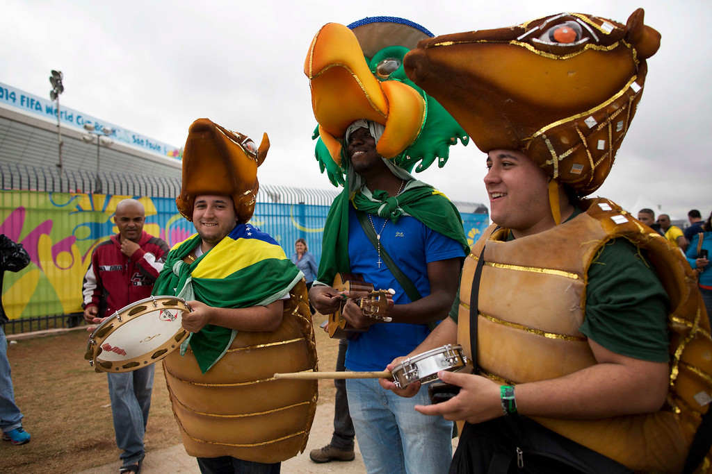 . Brazil soccer fans in costume play instruments outside Arena Corinthians stadium in Sao Paulo, Brazil, Wednesday, June 11, 2014. (AP Photo/Rodrigo Abd)