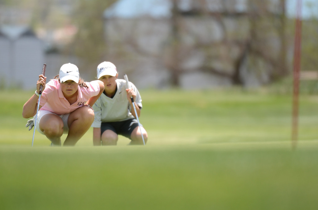 . ENGLEWOOD, CO. - MAY 21 : Kylee Sullivan of Cheyenne Mountain High School, left, and Kiselya Plewe of Dolores High School are checking the line of 12th green during State 4A Girl\'s Golf Championship at Broken Tree Golf Course. Englewood, Colorado. May 21, 2013. (Photo By Hyoung Chang/The Denver Post)