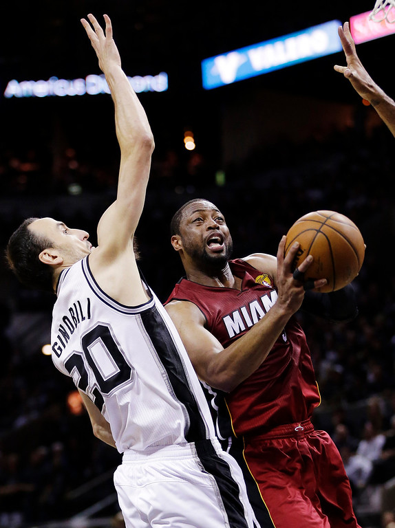 . Miami Heat guard Dwyane Wade, rightm, shoots as San Antonio Spurs guard Manu Ginobili (20) defends during the first half in Game 1 of the NBA basketball finals on Thursday, June 5, 2014, in San Antonio. (AP Photo/Eric Gay)