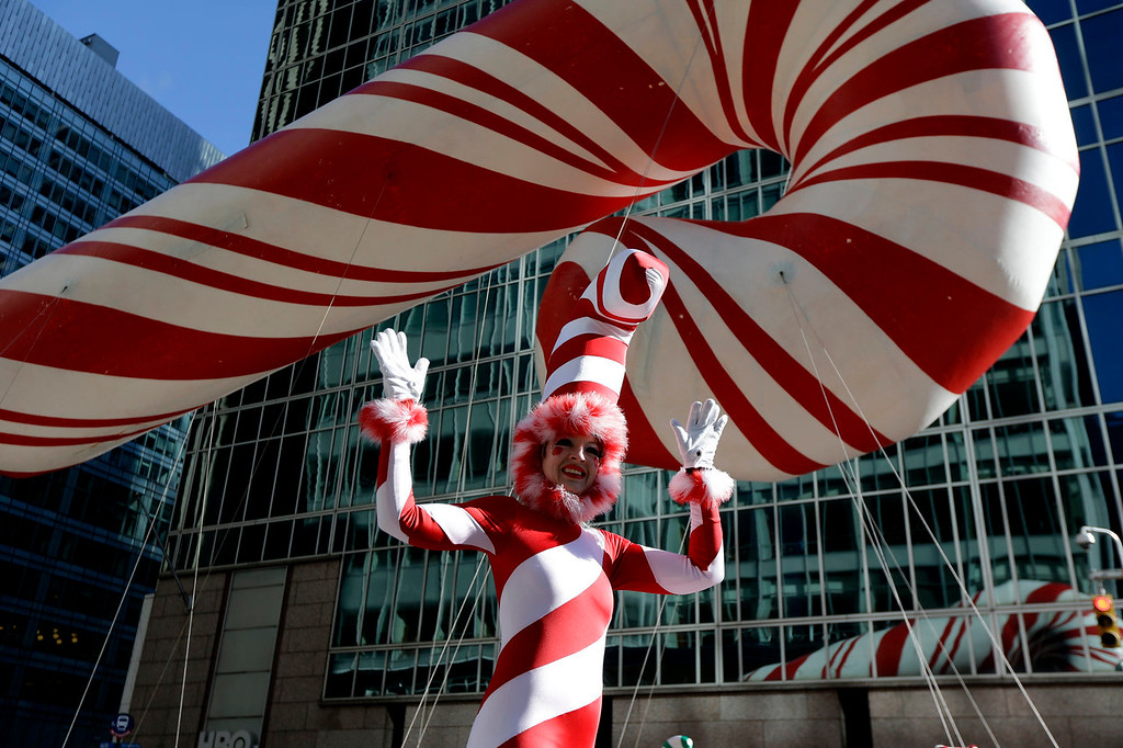 . A performer on stilts walks near a candy cane balloon during the Macy\'s Thanksgiving Day Parade, Thursday, Nov. 28, 2013, in New York. (AP Photo/Julio Cortez)