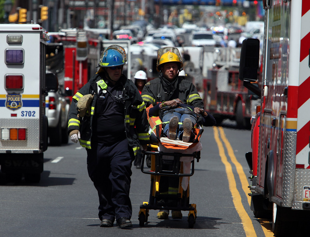 . Rescue personnel evacuate an injured person from the scene of a building collapse in downtown Philadelphia Wednesday June 5, 2013.   (AP Photo/Jacqueline Larma)
