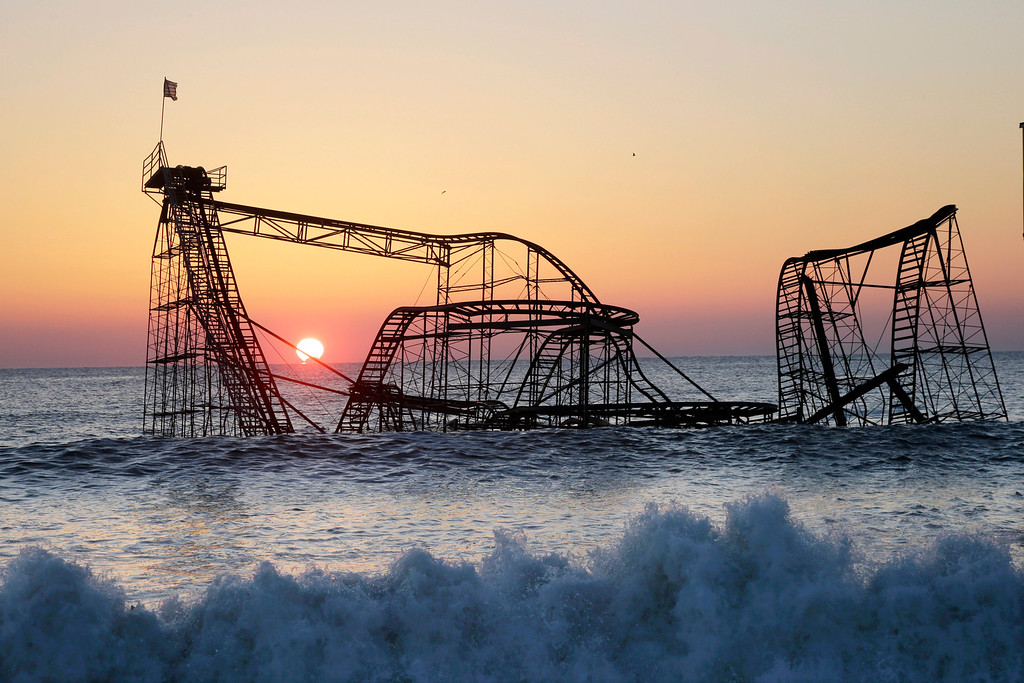 . FILE - In this Feb. 25, 2013 file photo, the sun rises in Seaside Heights, N.J., behind the Jet Star Roller Coaster which has been sitting in the ocean after part of the Funtown Pier was destroyed during Superstorm Sandy. Six months after the storm, the roller coaster is still in the ocean, although demolition plans are finally moving forward. (AP Photo/Mel Evans, File)