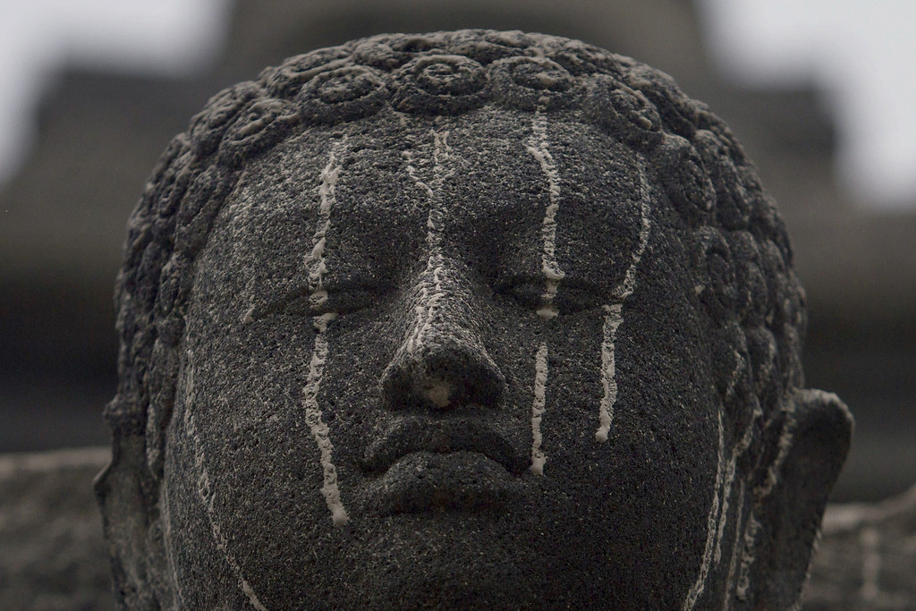 . A stone figure of buddha at the ancient Borobudur temple in Central Java is smeared with volcanic ash on February 14, 2014 following the eruption of Mount Kelud volcano.  AFP PHOTO / SURYO WIBOWO/AFP/Getty Images