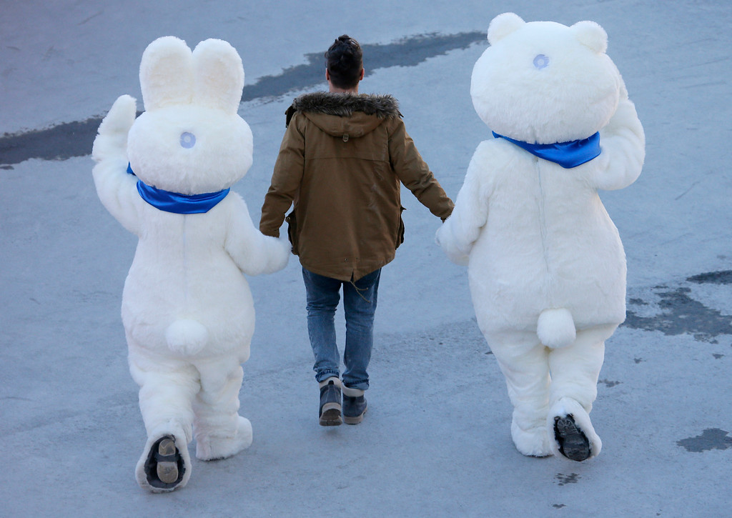 . A man leads the Olympic mascots to the cross-country portion of the Nordic combined at the 2014 Winter Olympics, Wednesday, Feb. 12, 2014, in Krasnaya Polyana, Russia. (AP Photo/Dmitry Lovetsky)