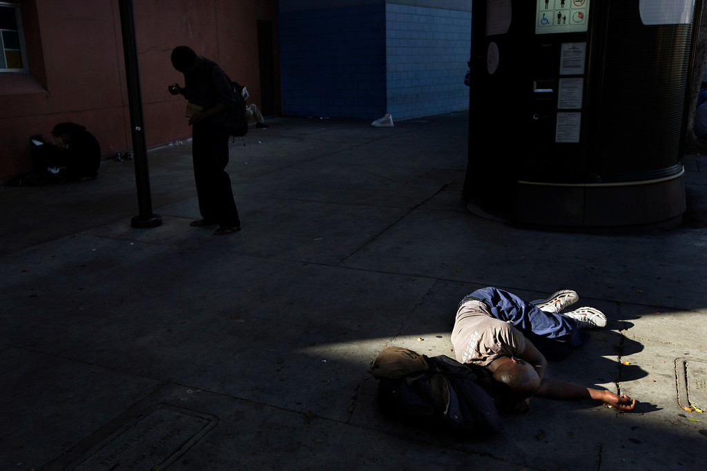 . The late afternoon sunlight shines on a homeless man as he sleeps on the street in the Skid Row area of Los Angeles, Wednesday, Sept. 4, 2013. (AP Photo/Jae C. Hong)