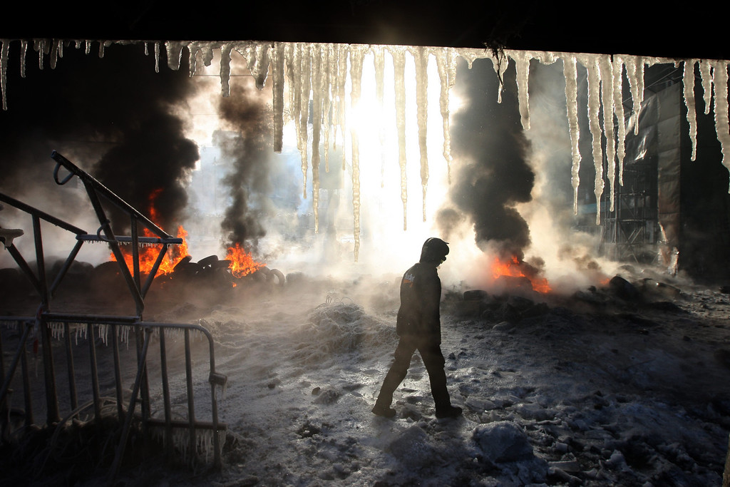 . A protester walks near burning tires during an anti-government protest in downtown Kiev, Ukraine, 25 January 2014. Ukraine has been convulsed by protests led by pro-European activists incensed that President Viktor Yanukovych opted against an association agreement with the European Union in November, choosing closer relations with Russia instead. According to media reports on 25 January, more fighting was reported overnight in Kiev, with demonstrators throwing rocks and flaming objects at security forces.  EPA/ZURAB KURTSIKIDZE