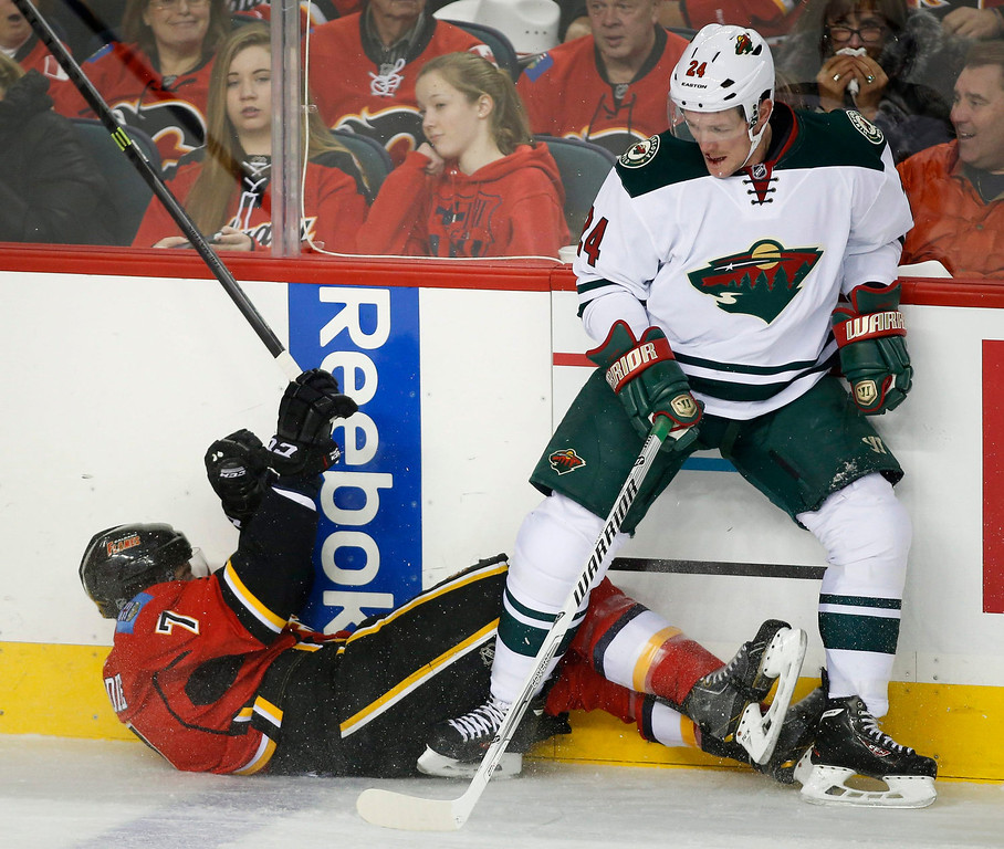 . Minnesota Wild Matt Cooke, right, knocks Calgary Flames\' TJ Brodie to the ice during first period of an NHL hockey game in Calgary, Alberta, Saturday, Feb. 1, 2014. (AP Photo/The Canadian Press, Jeff McIntosh)