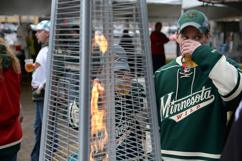 . Wild fans gathered around a propane heater outside the Xcel Energy Center during a chilly Minnesota evening Thursday.   (Photo by Karl Gehring/The Denver Post)