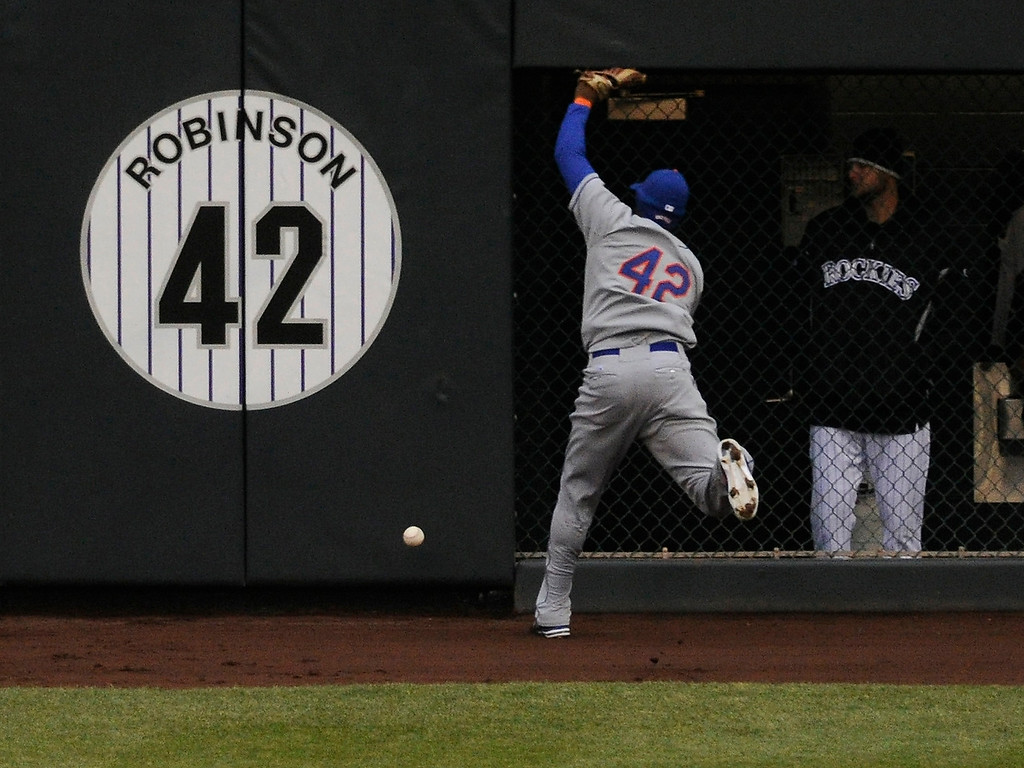 . DENVER, CO. - APRIL 16:  Mets right fielder Jordany Valdespin hit the wall trying to catch a ball off the bat of Eric Young in the eighth inning. Young tripled and drove in a run. The Colorado Rockies defeated the New York Mets 8-4 in a make up game Tuesday afternoon, April 16, 2013. Monday night\'s game was snowed out at Coors Field.  Photo By Karl Gehring/The Denver Post)